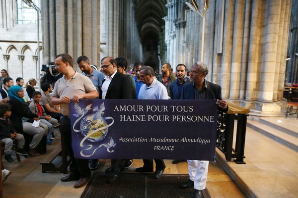 "Muslim men from the Ahmadiyya Muslim Association hold a banner reading ""Love for all, hatred for no one"" during a Mass in tribute to priest Jacques Hamel in the Rouen Cathedral on July 31, 2016. Muslims across France were invited to participate in Catholic ceremonies today to mourn a priest whose murder by jihadist teenagers sparked fears of religious tension. Masses will be celebrated across the country in honour of octogenarian Father Jacques Hamel, whose throat was cut in his church on July 26, 2016 in the latest jihadist attack on France. / AFP / CHARLY TRIBALLEAU        (Photo credit should read CHARLY TRIBALLEAU/AFP/Getty Images)"
